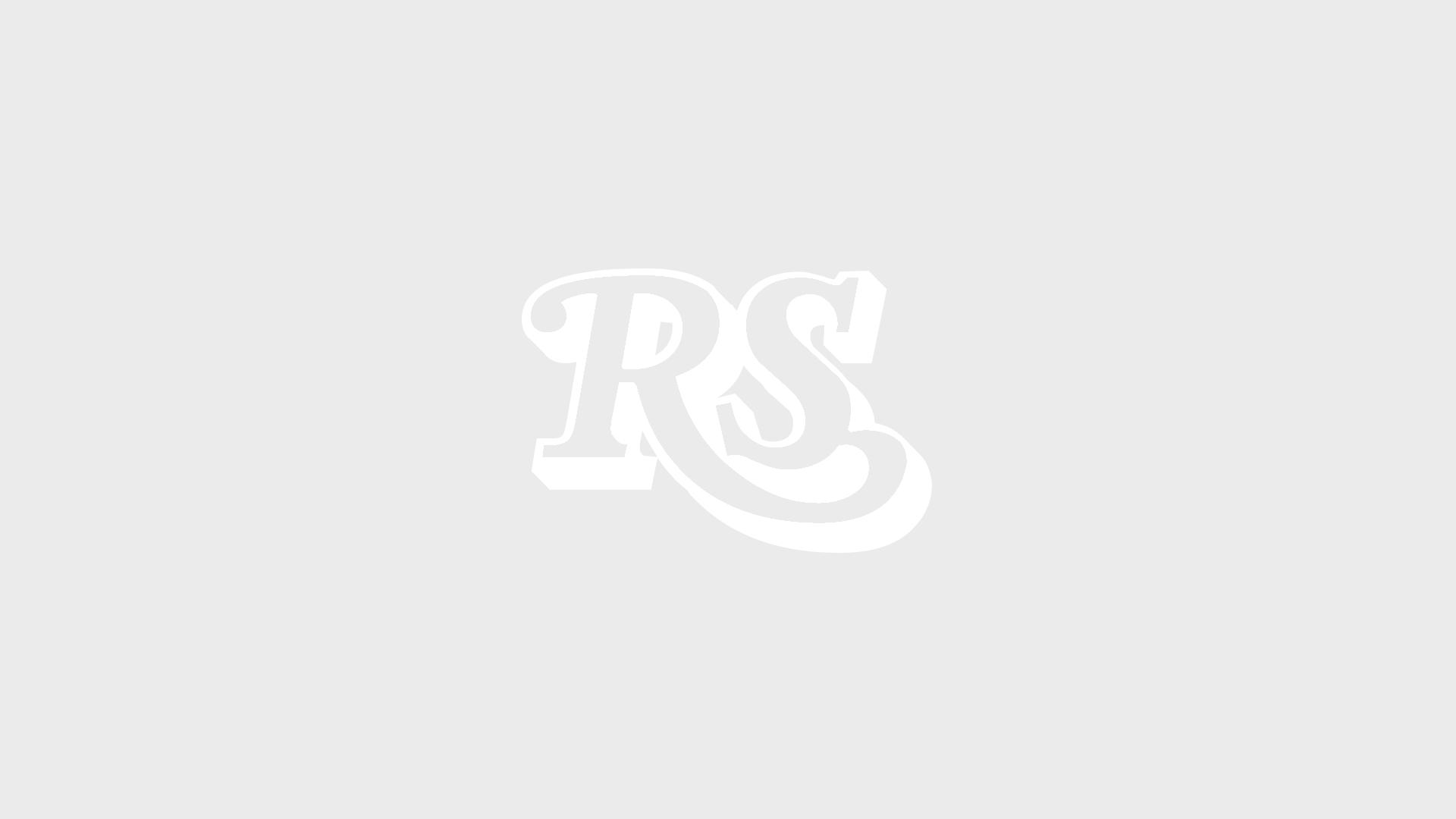 Die Ramones 1977 bei einem Konzert mit ihrem bandeigenen 'Presidential Seal'-Logo im Hintergund. Auf den Fahnen geschreiben: