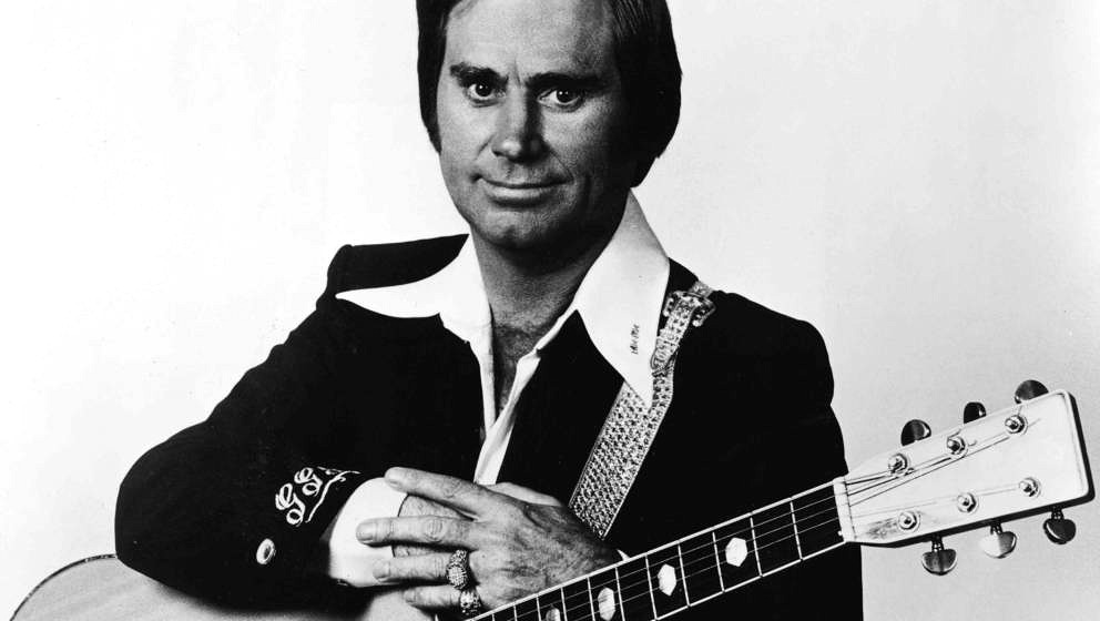 Promotional studio portrait of American country singer and songwriter George Jones with an acoustic guitar, circa 1970. (Phot