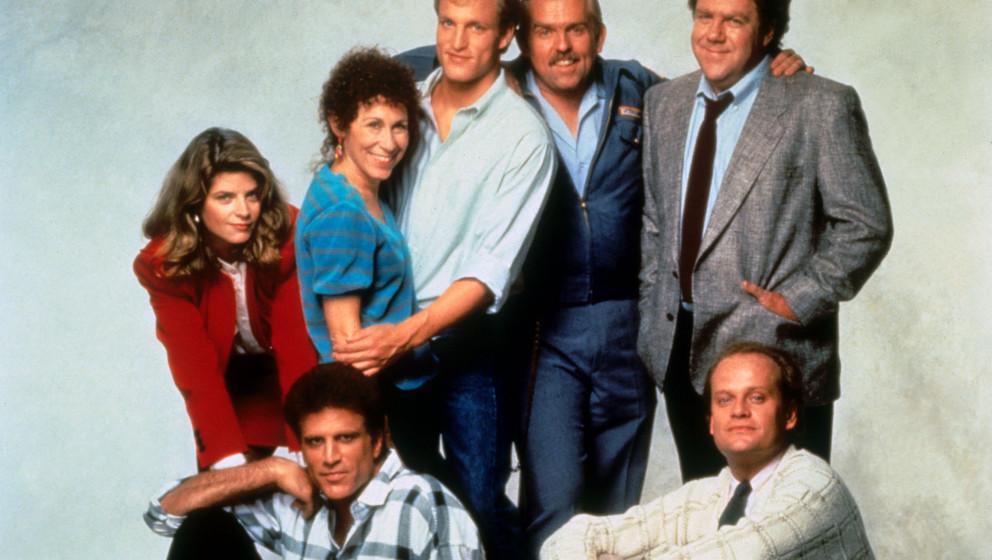 CHEERS [US TV 1982 -1993]  [Back row L-R] KIRSTIE ALLEY as Rebecca Howe, RHEA PERLMAN as Carla Tortelli, WOODY HARRELSON as W
