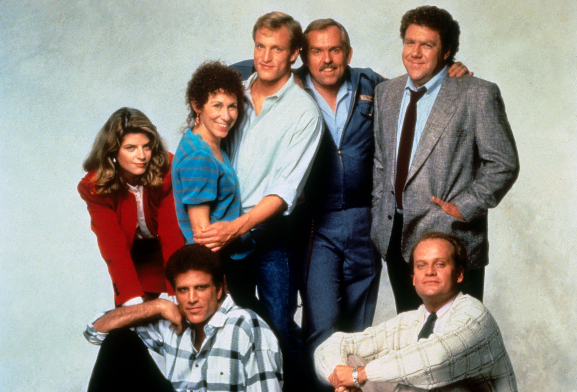 CHEERS [US TV 1982 -1993]  [Back row L-R] KIRSTIE ALLEY as Rebecca Howe, RHEA PERLMAN as Carla Tortelli, WOODY HARRELSON as W