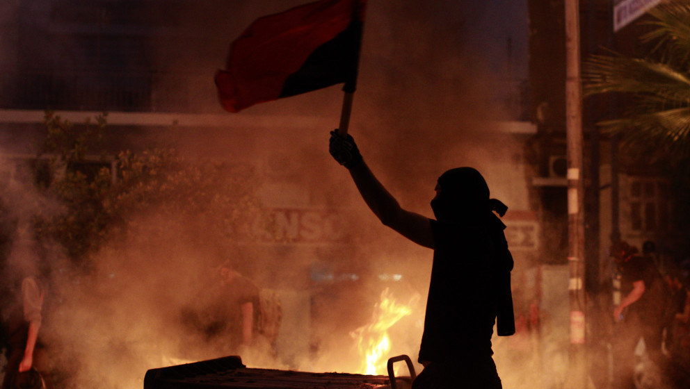 A protester waves a flag in front of a burning barricade during a protest, after the stabbing of a 34 year old man in the sub