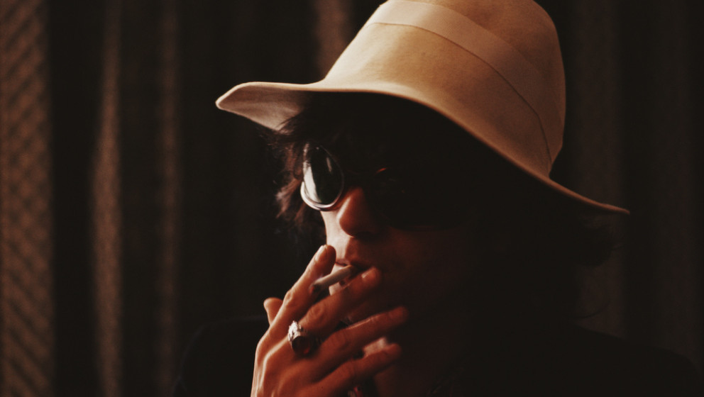 Keith Richards from the Rolling Stones smokes a cigarette while wearing sunglasses and a cream coloured hat circa 1967. (Phot