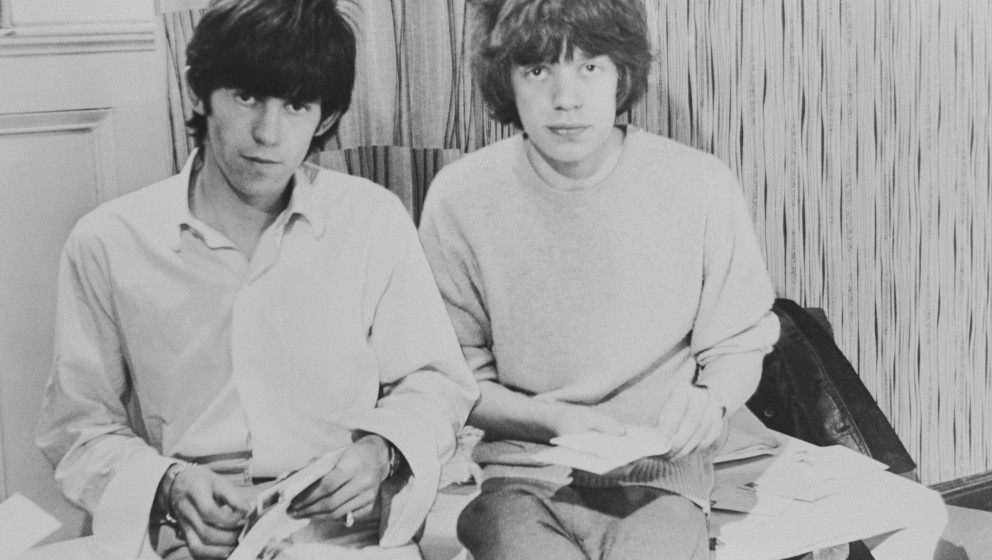 Rolling Stones singer Mick Jagger and guitarist Keith Richards opening fan mail during the early days of the band, circa 1963