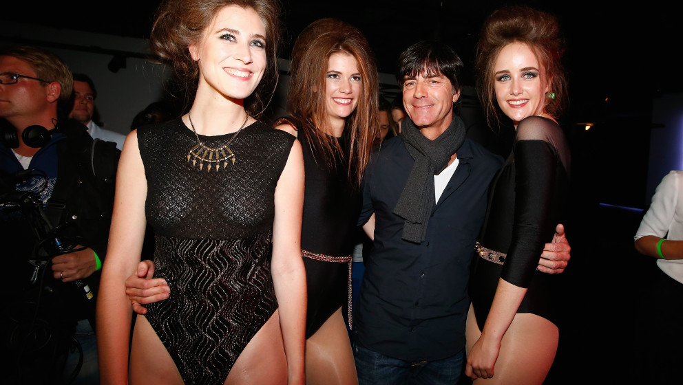 BERLIN, GERMANY - SEPTEMBER 13:  Joachim Loew poses with hostesses during the No1 TRUE BERLIN BY Shan Rahimkhan & ghd on