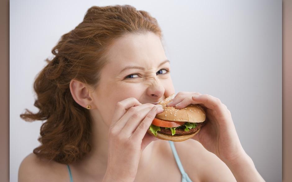 Young woman eating hamburger, portrait, close-up