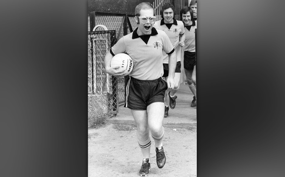 Pop singer, pianist and football club chairman Elton John leads Watford Football Club team out onto the pitch.   (Photo by Ti