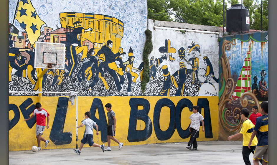 Children playing soccer in La Boca neighbourhood with painted mural behind.
