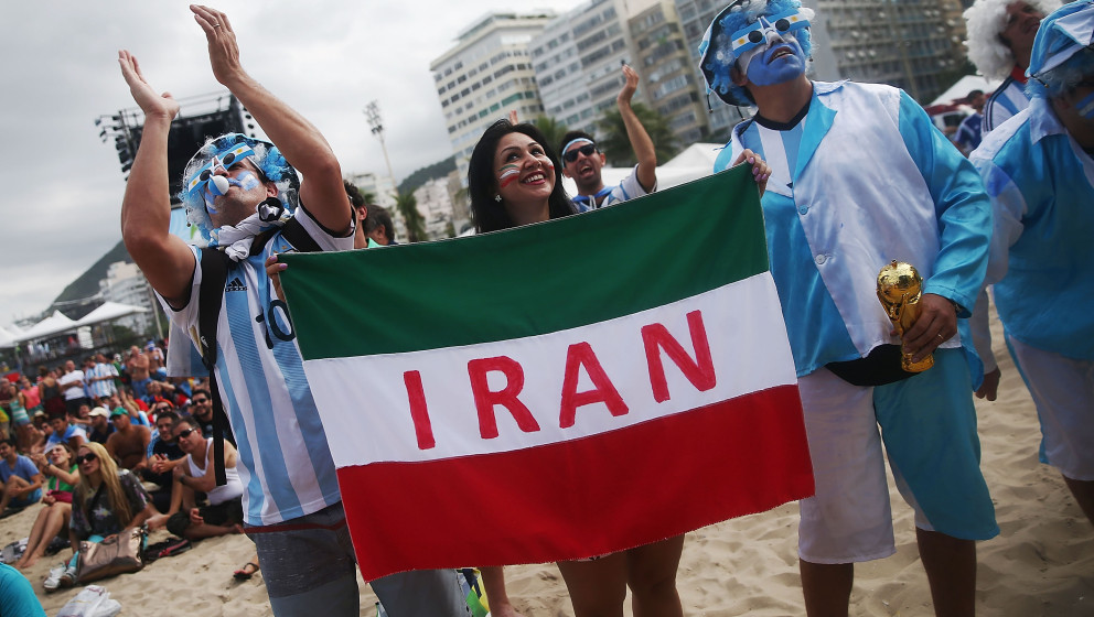 RIO DE JANEIRO, BRAZIL - JUNE 21: Argentina fans pose next to an Iranian supporter (C) before Iran lost to Argentina while wa