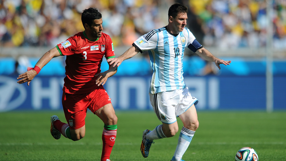 BELO HORIZONTE, BRAZIL - JUNE 21: Lionel Messi of Argentina in action with Ehsan Haji Safi of Iran during the 2014 FIFA World