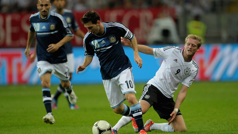 FRANKFURT AM MAIN, GERMANY - AUGUST 15:  Andre Schuerrle of Germany and Lionel Messi of Argentina battle for the ball during