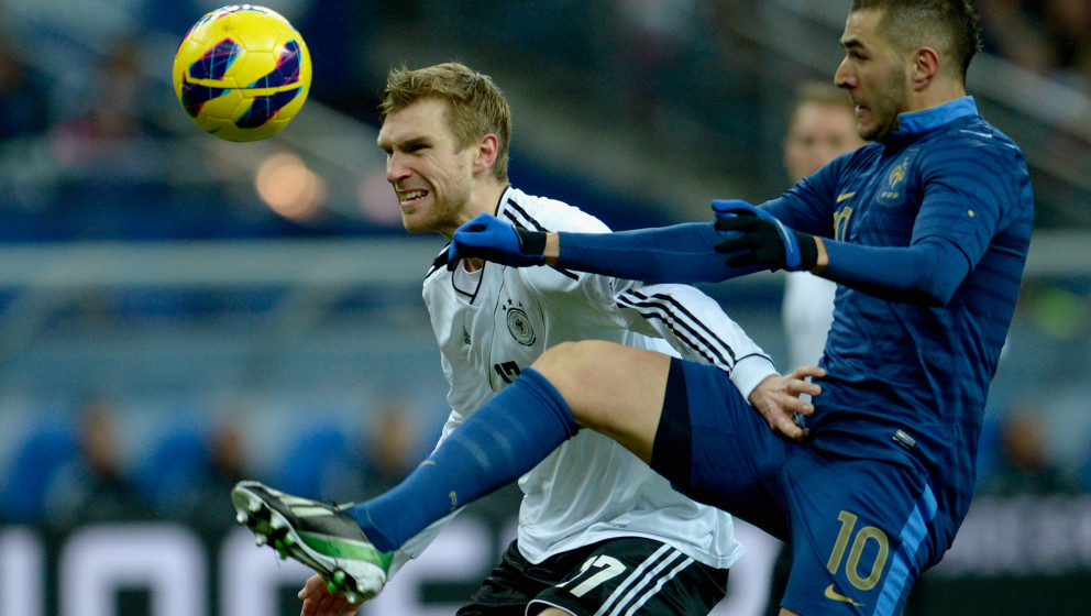 PARIS, FRANCE - FEBRUARY 06:  Per Mertesacker of Germany challenges Karim Benzema of France during the international friendly