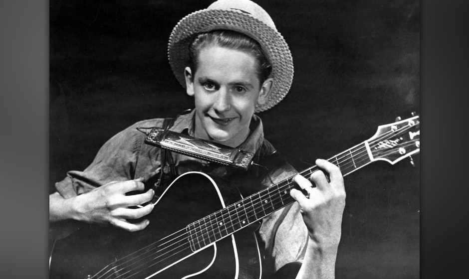 CIRCA 1936:  Guitarist and inventor Les Paul poses for a portrait holding a guitar and the neck-worn harmonica holder he inve