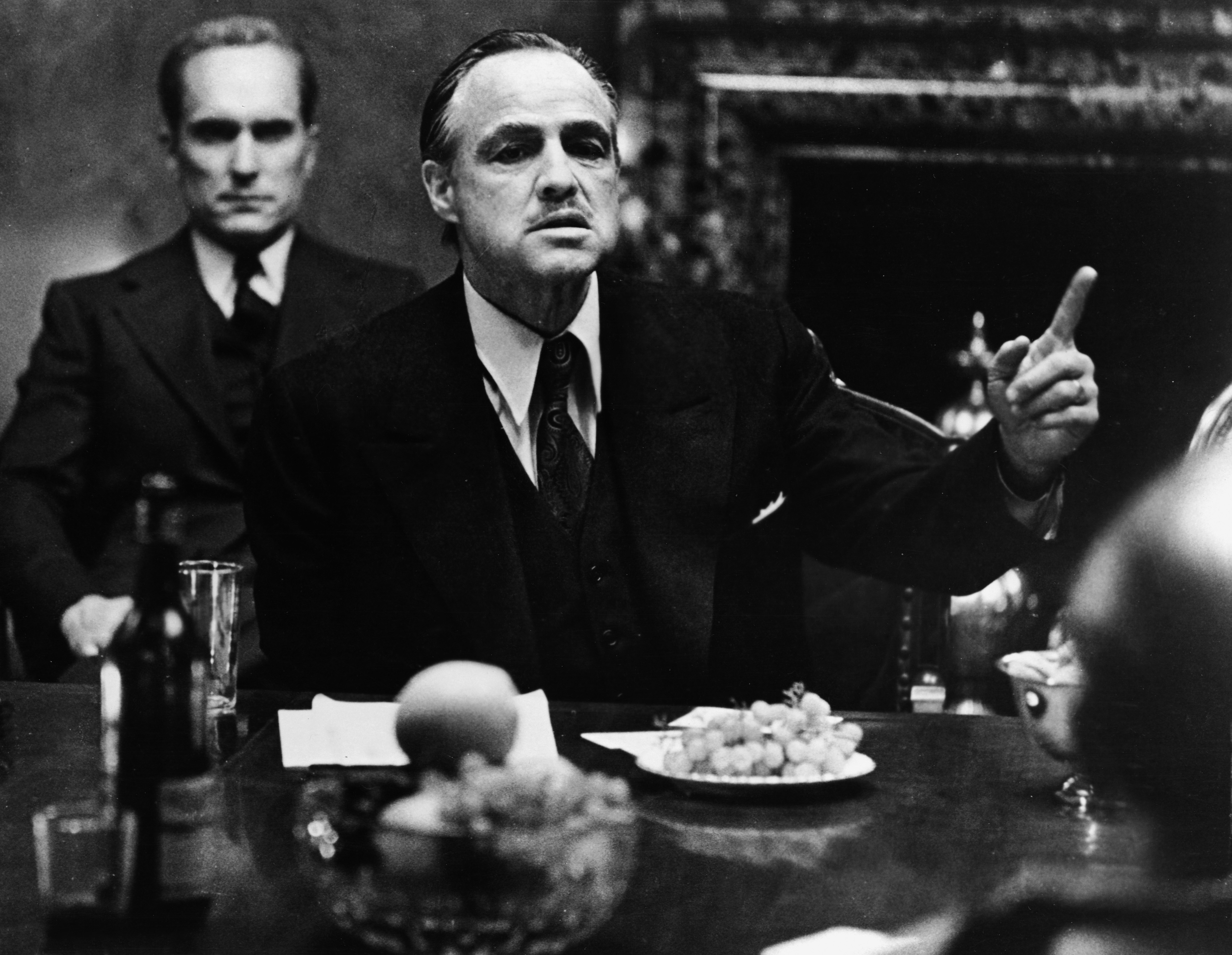American actor Marlon Brando gestures at a table while American actor Robert Duvall sits behind him in a still from the film,