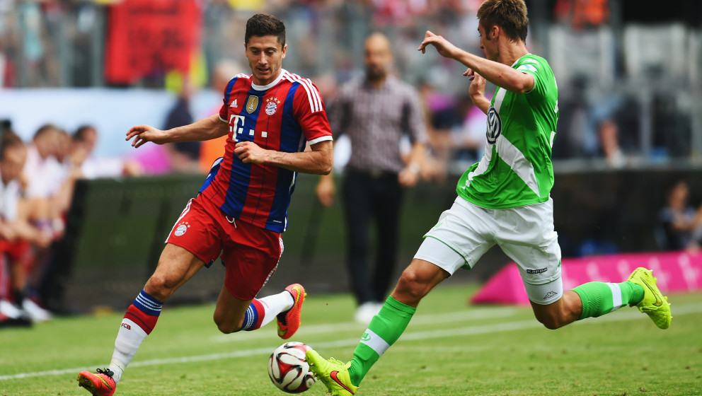 HAMBURG, GERMANY - JULY 27:  Robert Lewandowski of FC Bayern Muenchen is challenged by Robin Knoche of VfL Wolfsburg during t