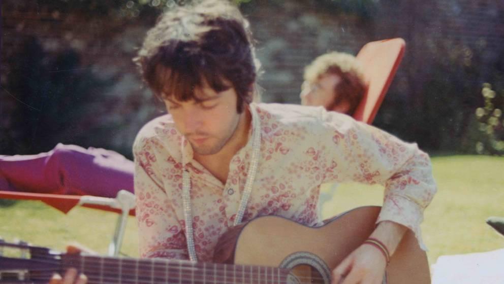 LONDON - 1st JANUARY: Paul McCartney from the Beatles plays an acoustic guitar while John Lennon (1940-1980) sunbathes behind