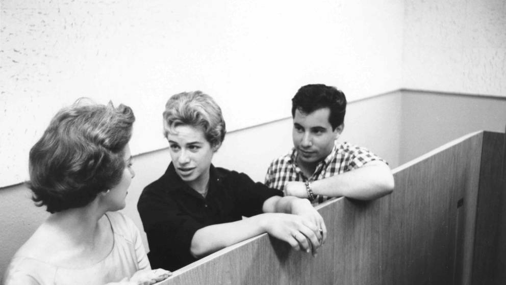 NEW YORK, NY - CIRCA 1959: Singer songwriters Carole King (center) and Paul Simon talk between takes in a New York, New York