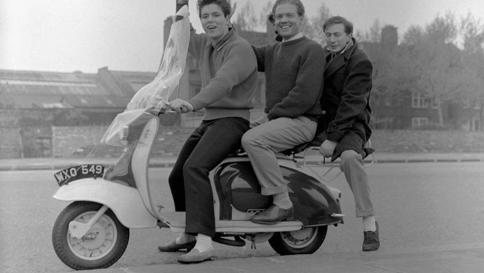 Cliff Richard, posed, on scootter with an unknown man and talent scout and manager Ray Mackender, 1958. (Photo by Harry Hammo