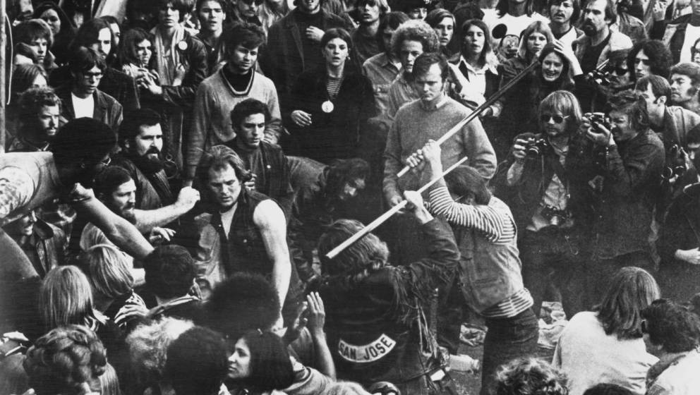 A still from the documentary film 'Gimme Shelter', showing audience members looking on as Hells Angels beat a fan with pool c