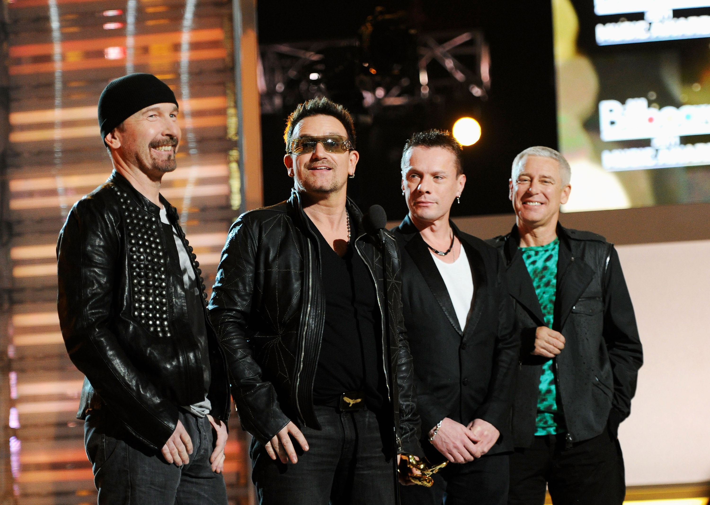 Musicians The Edge, Bono, Larry Mullen Jr. and Adam Clayton of the band U2 speak onstage during the 2011 Billboard Music Awar