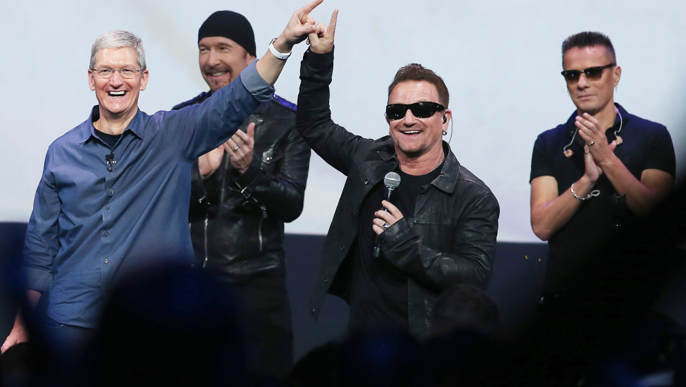 CUPERTINO, CA - SEPTEMBER 09:  Apple CEO Tim Cook (L) greets the crowd with U2 singer Bono (2nd R) as The Edge (2nd L) and La