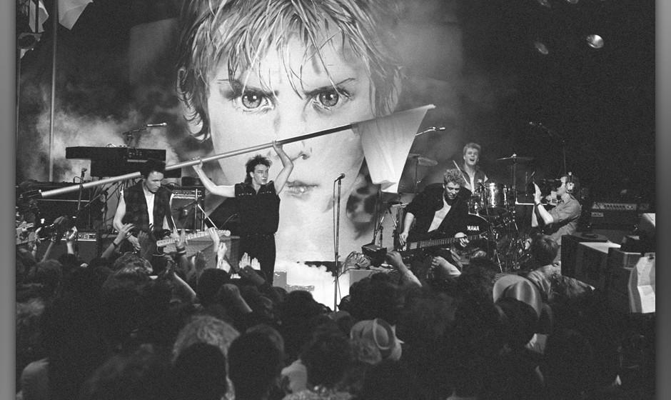 UNITED KINGDOM - MARCH 16:  Photo of U2; L-R: The Edge, Bono (waving flag), Adam Clayton, Larry Mullen Jnr performing live on