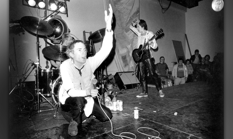 8th December 1976:  The Sex Pistols: Johnny Rotten (John Lydon), Paul Cook (drums) and Steve Jones (guitar) performing on sta