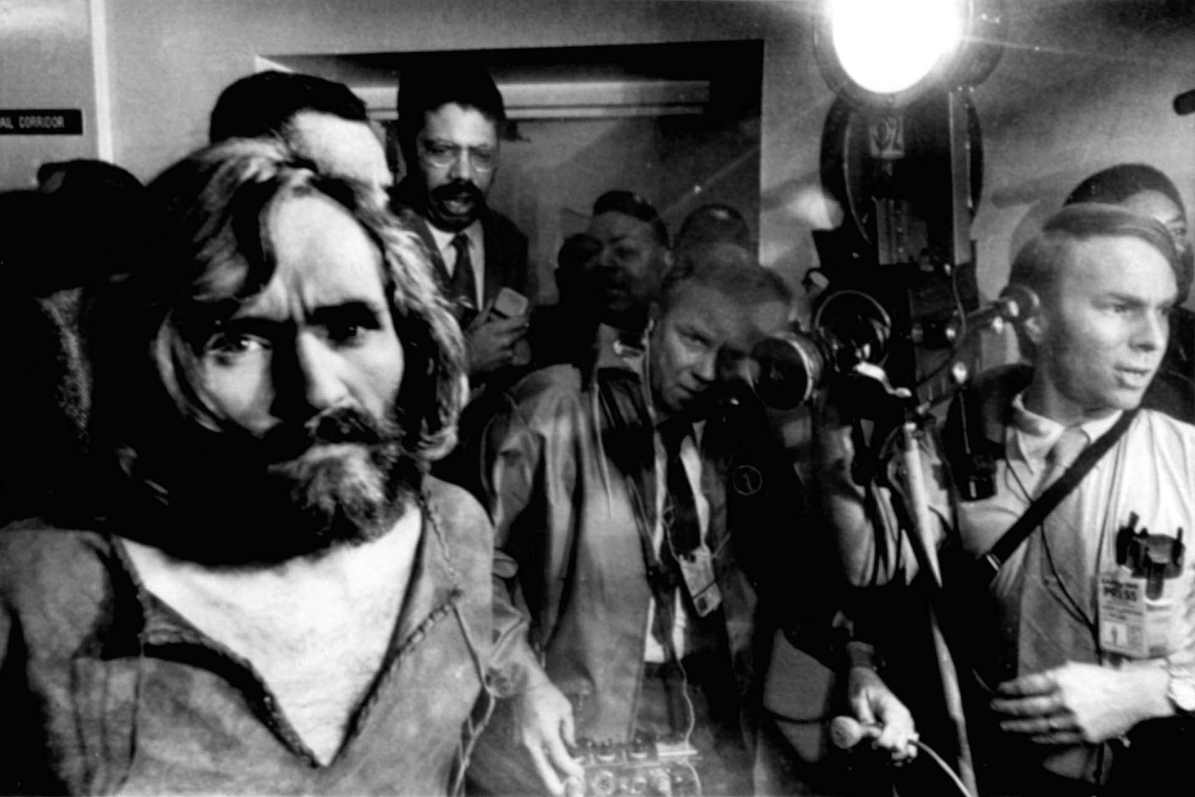 Charles Manson, the 35-year-old cult leader, is escorted through a crowd of newsmen as he arrives at the Los Angeles city jai