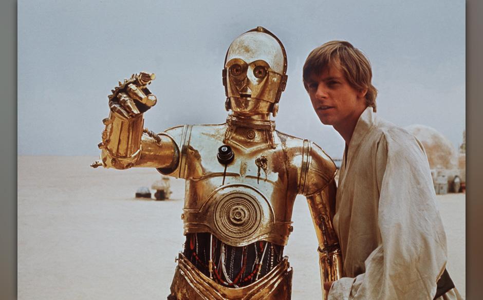 Mark Hamill als Luke Skywalker (r) mit dem goldenen Androiden C 3PO in einer Szene des Science Fiction-Films 'Star Wars' von
