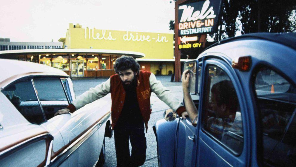 George Lucas, US film director, posing between two cars, with 'Mel's Drive-in' in the background, on the set of 'American Gra