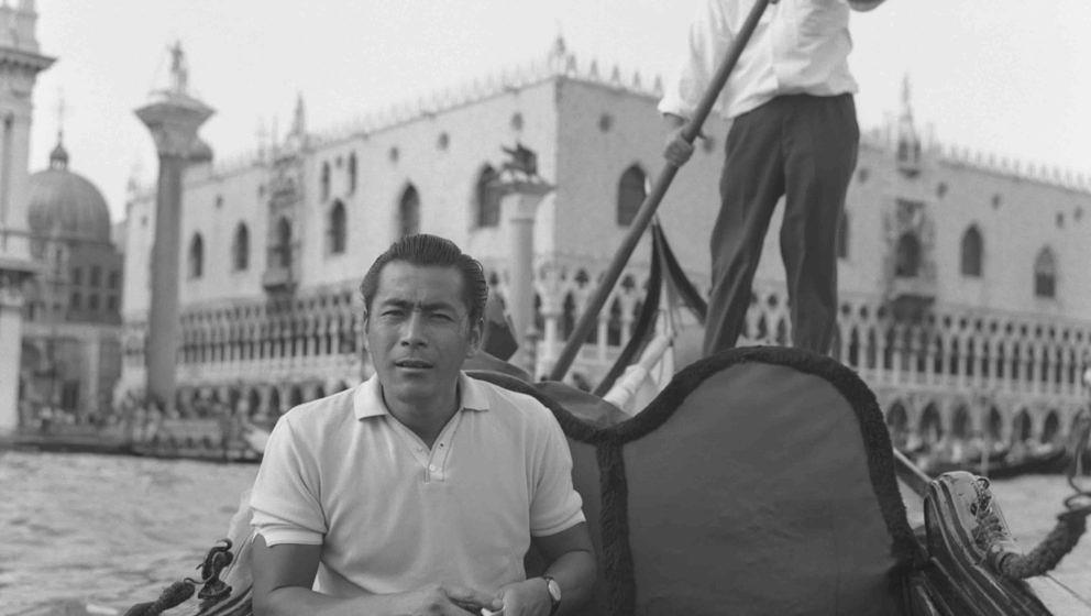 Japanese actor Toshiro Mifune, sitting on a gondola with a cinecamera next to him, a gondolier rowing behind him and St. Mark