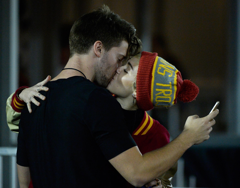 LOS ANGELES, CA - NOVEMBER 13:  Miley Cyrus (R) kisses Patrick Schwarzenegger during the game between the California Golden B
