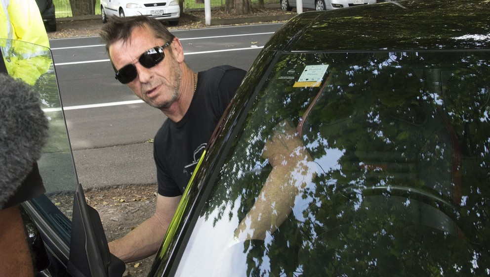 Former AC/DC drummer Phil Rudd climbs into his car as he leaves court after faces charges at the High Court in Tauranga, New