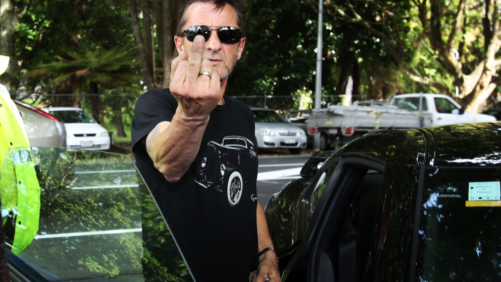 TAURANGA, NEW ZEALAND - NOVEMBER 26:  AC/DC drummer Phil Rudd gestures to members of the media after leaving Tauranga Distric