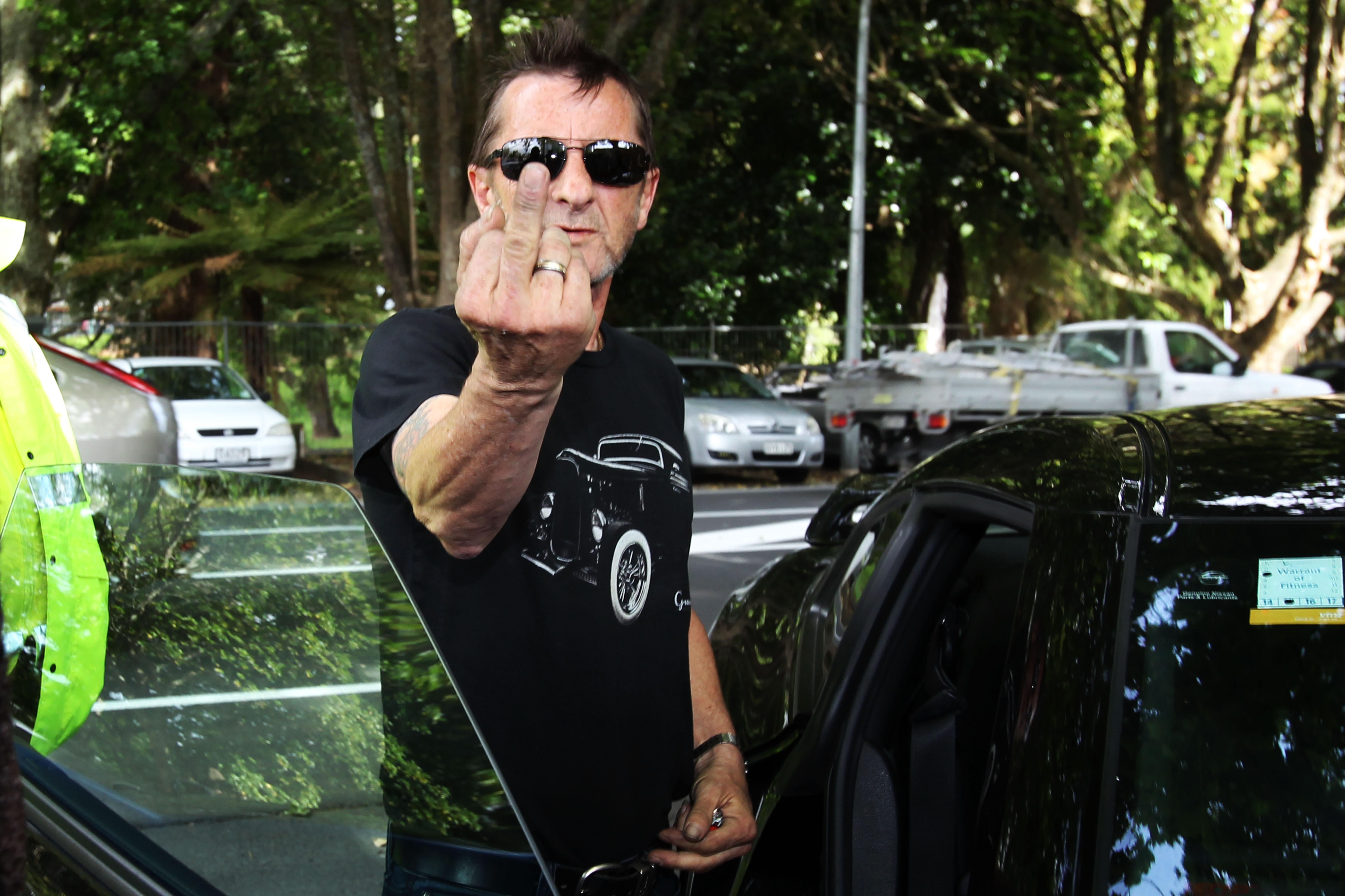 TAURANGA, NEW ZEALAND - NOVEMBER 26:  AC/DC drummer Phil Rudd gestures to members of the media after leaving Tauranga Distric