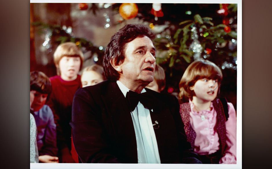 CIRCA 1975:  Country singer/songwriter Johnny Cash in front of a Christmas tree surrounded by children in circa 1975. (Photo