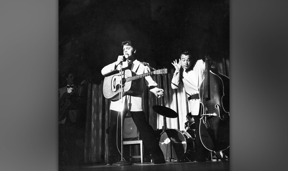 American actor and singer Elvis Presley singing on stage with musician Bill Block, circa 1950s. (Photo by Pictorial Parade/Ar