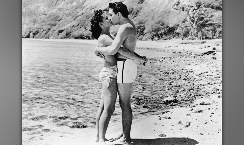 American singer and actor Elvis Aron Presley (1935 - 1977) (as Chad Gates), dressed in swimming trunks, exchanges a passionat