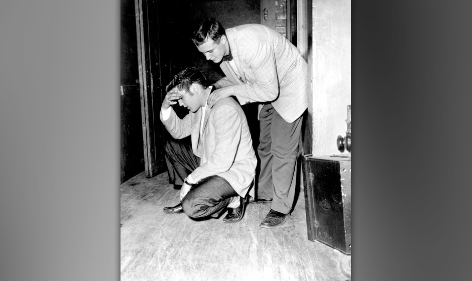 ST. PAUL, MN - MAY 13:  Rock and roll singer Elvis Presley gets consoled while kneeling backstage on May 13, 1956 in St. Paul