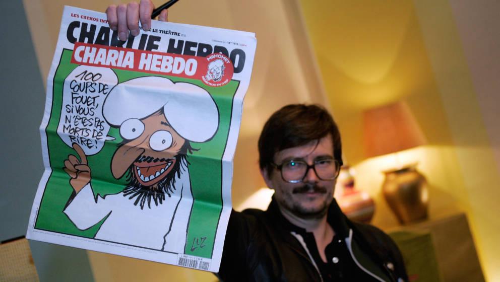 PARIS, FRANCE - NOVEMBER 03:  The Charlie Hebdo' s cartoonist Luz shows a special edition of French satirical magazine Charli