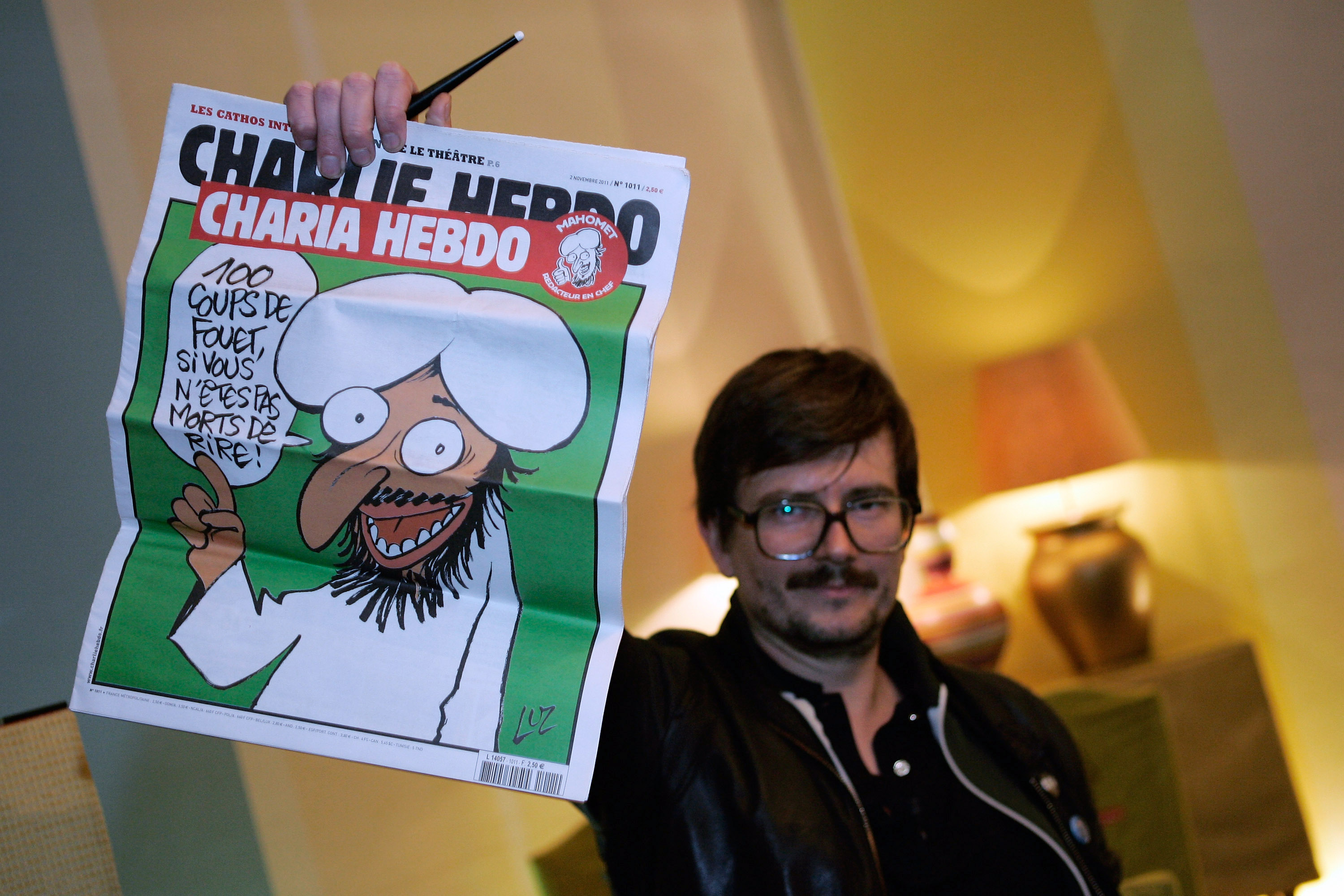 PARIS, FRANCE - NOVEMBER 03:  The Charlie Hebdo' s cartoonist Luz shows a special edition of French satirical magazine Charli
