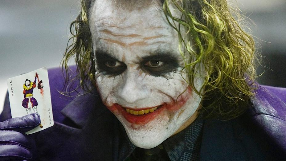 The Dark Knight (2008).  Zwei mit Karnevalskostümen verkleidete Männer verhandeln die Rollen von Gut und Böse neu. Die Wel