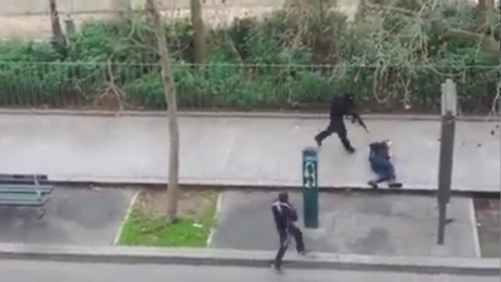 A police officer pleads for mercy on the pavement before being shot in the head by masked gunmen during an attack on the head