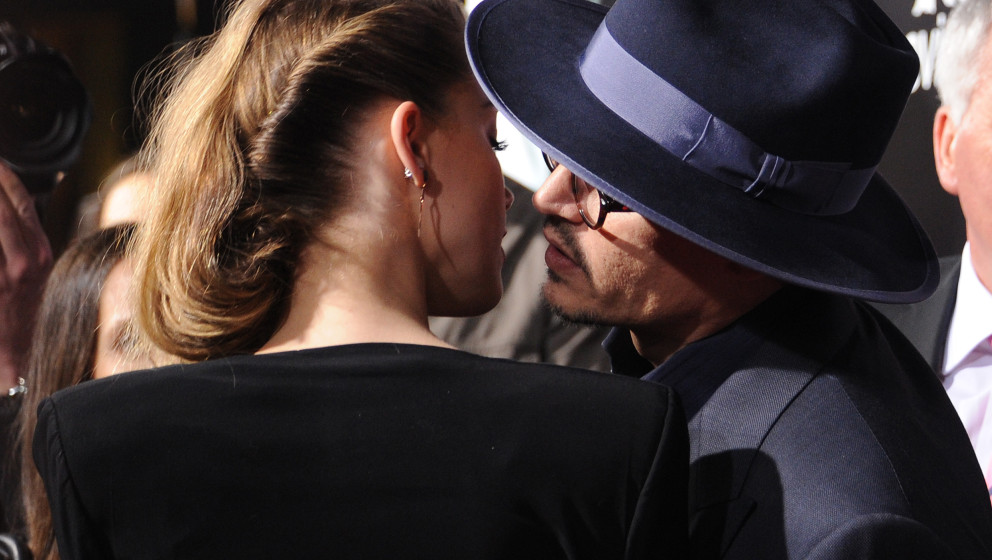Actor Johnny Depp  (R) leans over to kiss actress Amber Heard (L) as they attend the US premiere of '3 Days To Kill,' at Arcl