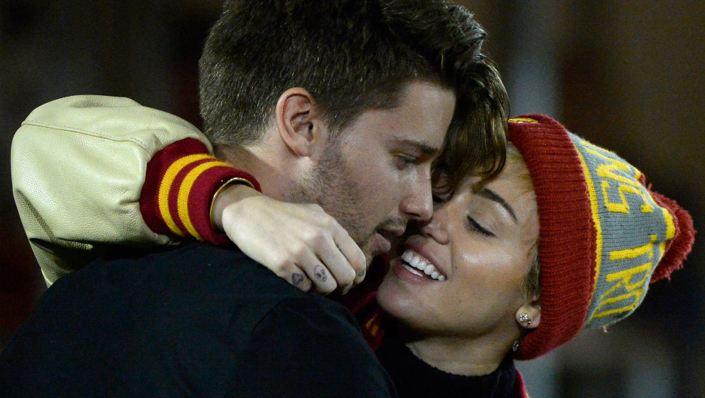 LOS ANGELES, CA - NOVEMBER 13:  Miley Cyrus (R) kisses Patrick Schwarzenegger during the game between the California Golden B