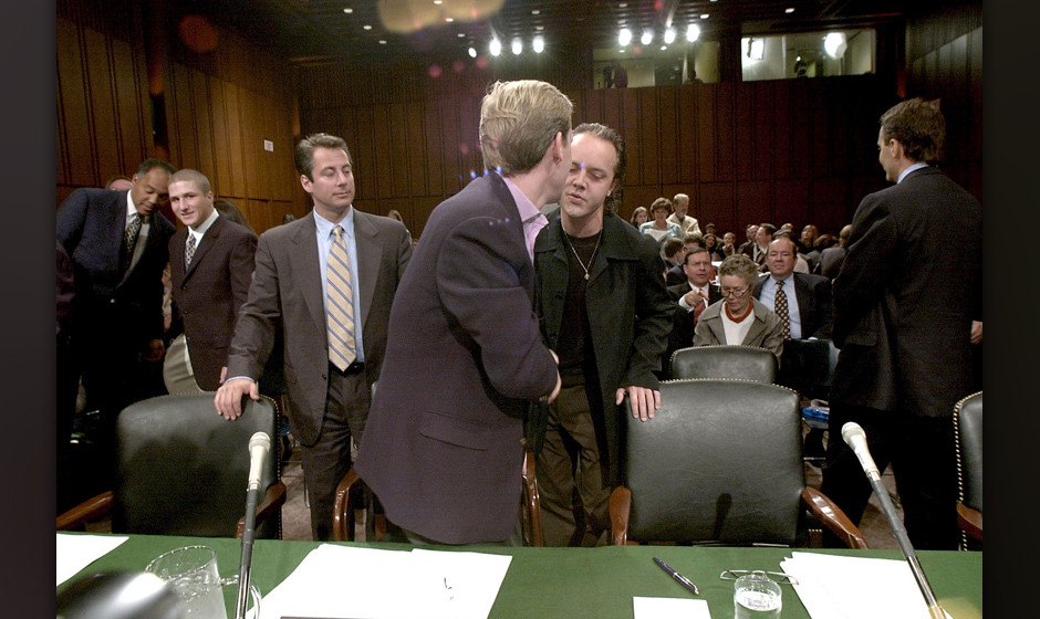 372649 07: Shawn Fanning, 2nd left, the co-founder of the online music service Napster, talks with his lawyer July 11, 2000 d