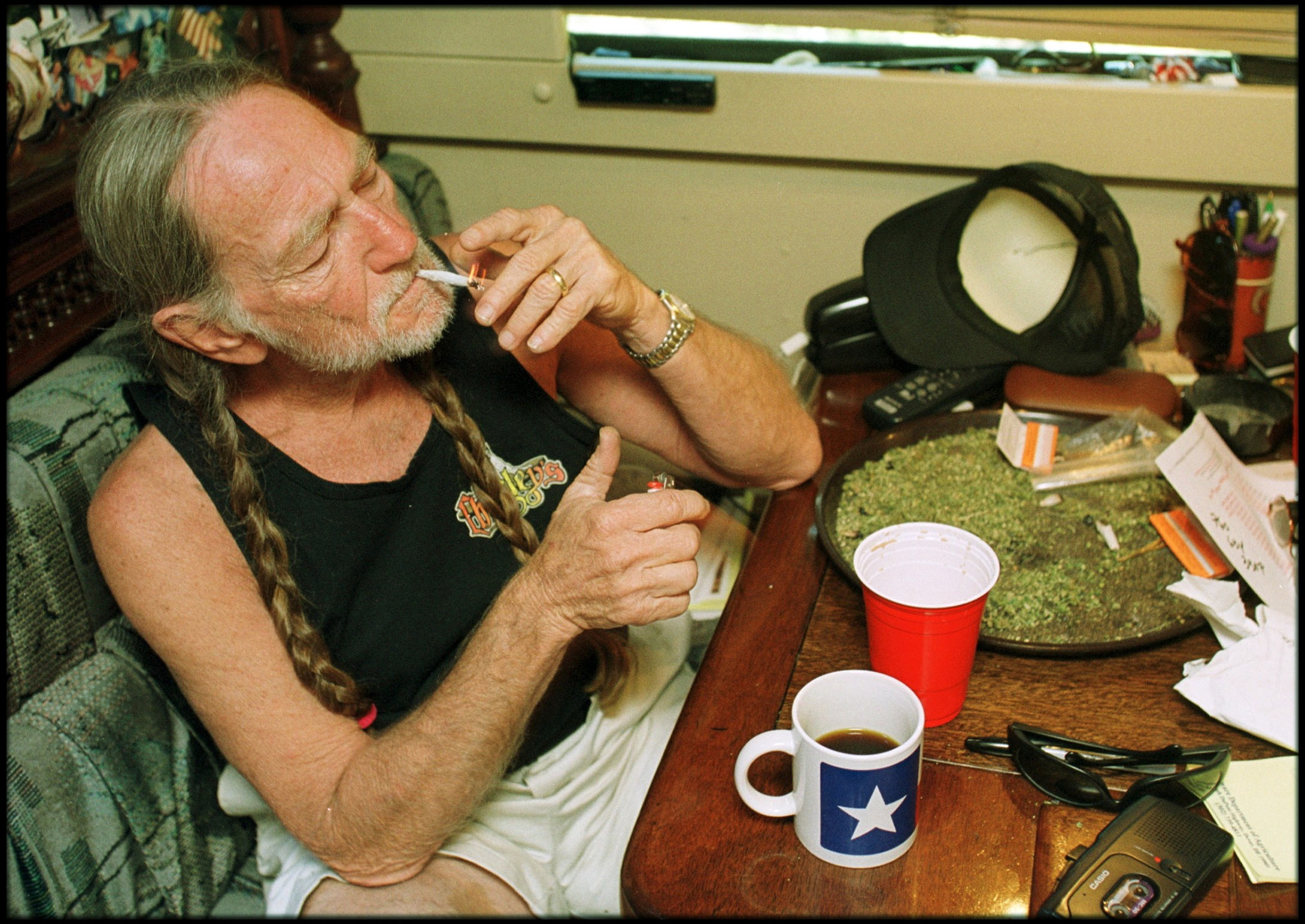 American country singer Willie Nelson takes a drag off a joint while relaxing at his home in Texas, 2000s. A large amount of