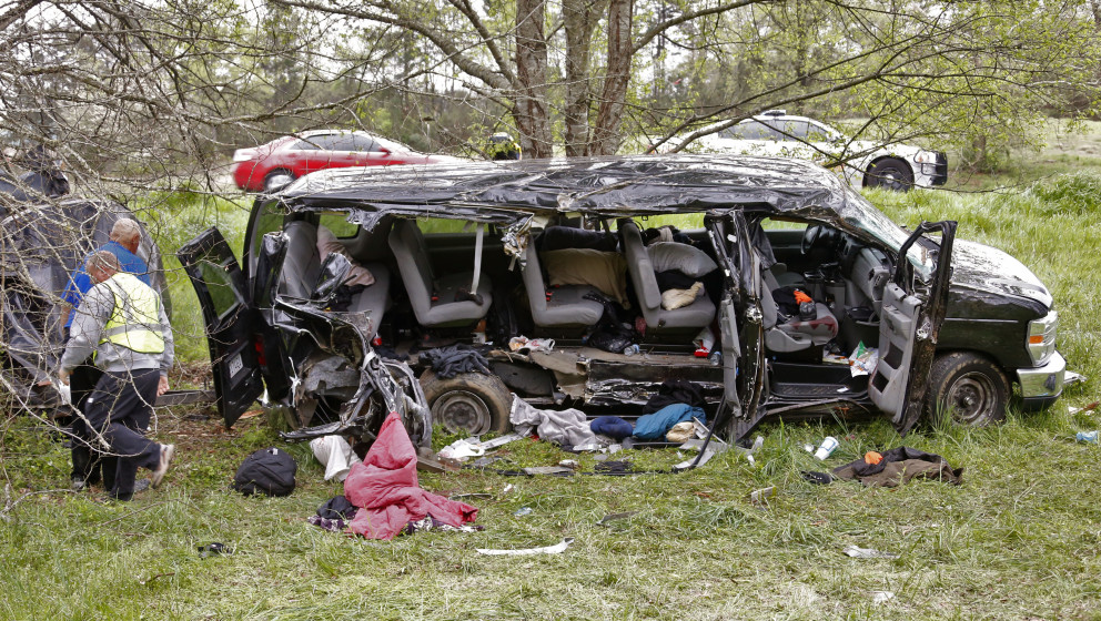 Investigators work at the scene where three people died early Monday, April 6, 2015, when a van carrying members of two heavy