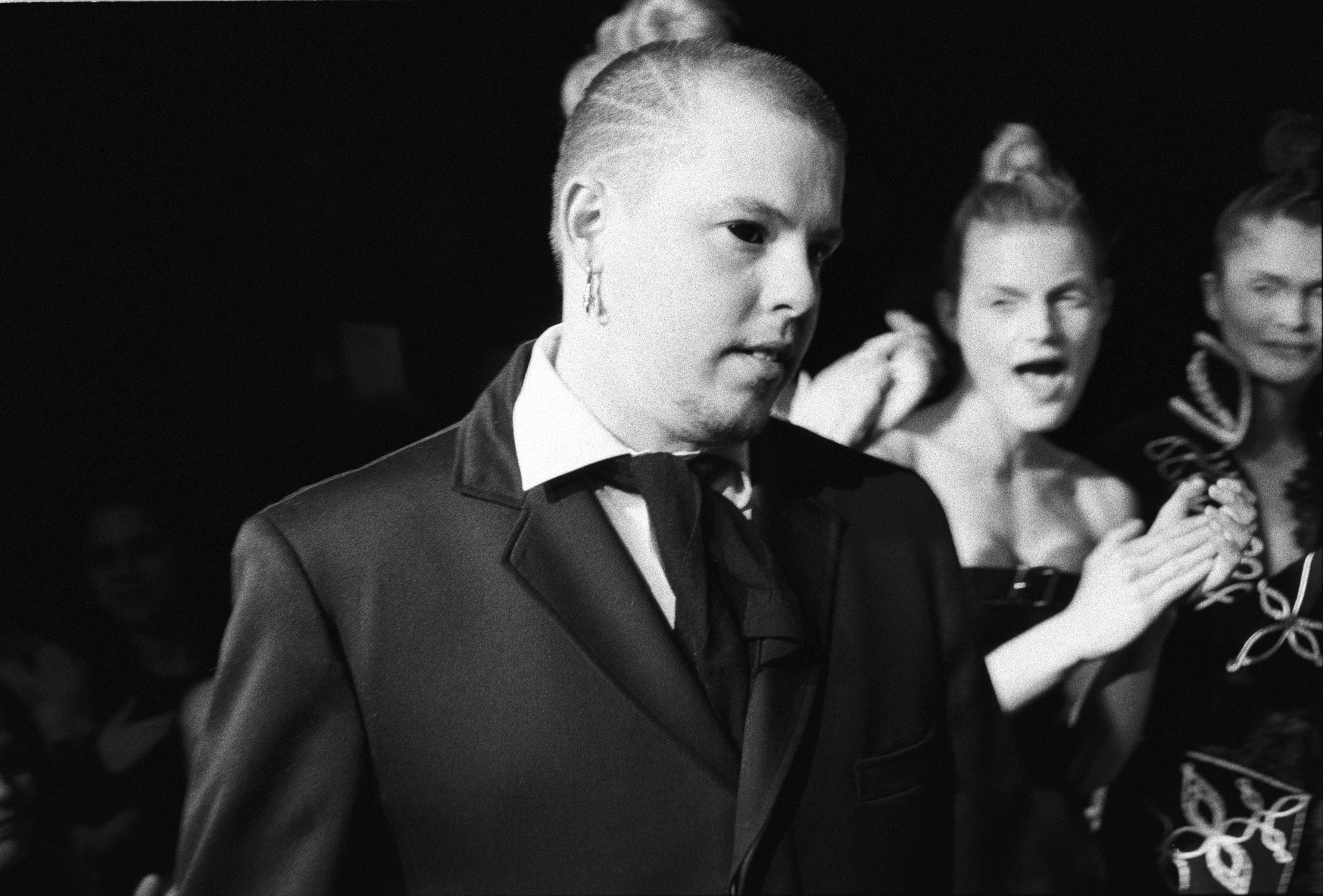 NEW YORK - MARCH 1996:  British fashion designer Alexander McQueen with unidentified models in the background at a show of hi