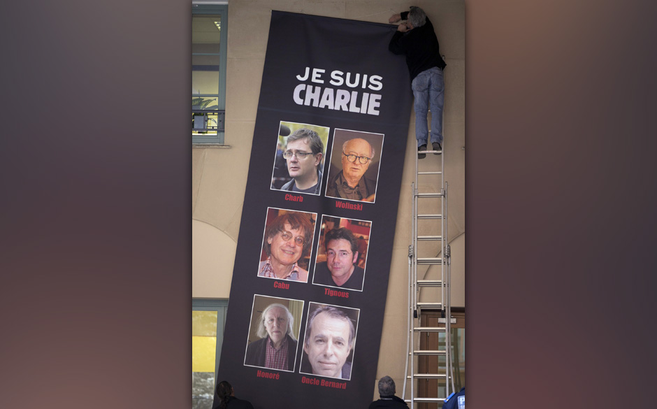 Peope put up a banner reading 'Je suis Charlie' (I am Charlie) featuring the portraits of late Charlie Hebdo editor Stephane