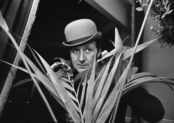 English actor Patrick Macnee concealed behind a houseplant, 20th May 1965. (Photo by David Cairns/Getty Images)